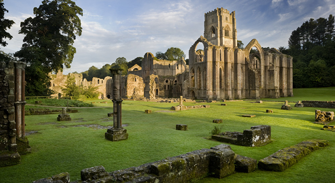 A view towards the east end of the Abbey church showing the great east window arch at Fountains Abbey, North Yorkshire. Remains of the monks' infirmary are visible in the foreground. The Cistercian community of monks was founded here in 1132 but was dissolved in 1539.